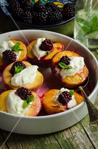 Gratinated peaches with cream cheese, blackberries and mint