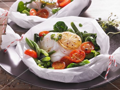 Cod with vegetables and lemons in parchment paper