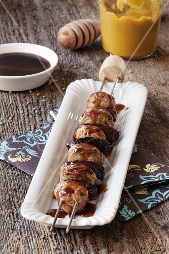 A sausage kebab with dates and a honey mustard sauce