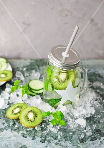 A glass of cucumber and kiwi drink with a straw