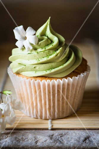 A cupcake with matcha frosting and a jasmine flower
