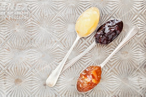 Lemon curd, black cherry jam and orange marmalade on vintage spoons