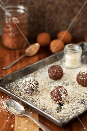 Date energy balls being rolled in desiccated coconut