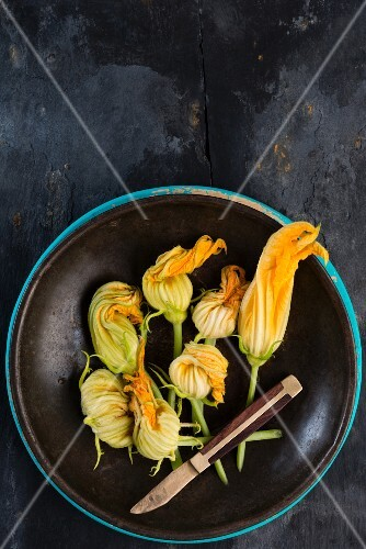 Courgette flowers in a brown bowl