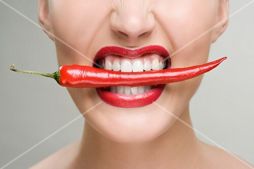 A woman biting on a chili pod