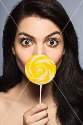A woman with long black hair holding a yellow lollipop in front of her mouth