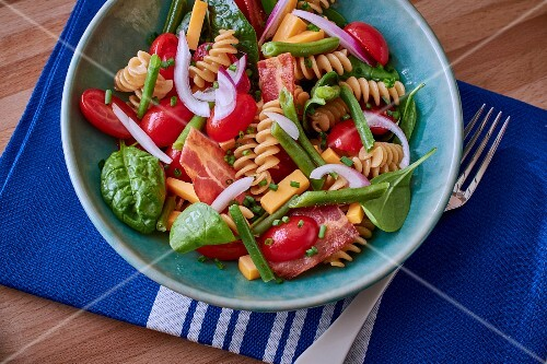 Pasta salad with tomatoes, spinach and bacon