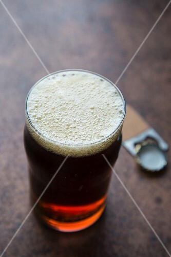 A glass of amber ale with a bottle opener and a bottle cap
