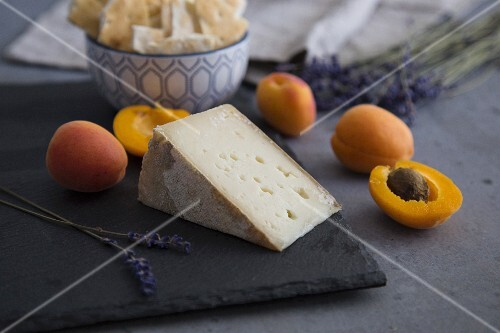 Apricots and goat's cheese on a slate platter with crackers and lavender flowers