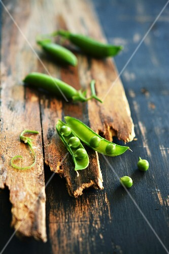 Pea pods on a rustic wooden surface