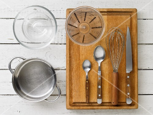 Kitchen utensils: a saucepan, a glass bowl, a measuring cup, spoons, a whisk and a knife