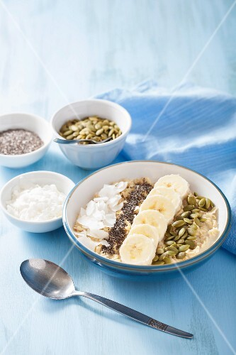 Porridge with bananas, pumpkin seeds, chia seeds and coconut flakes