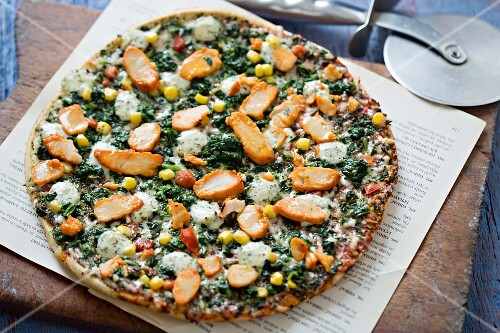 A whole pizza with chicken, spinach, sweetcorn and peppers