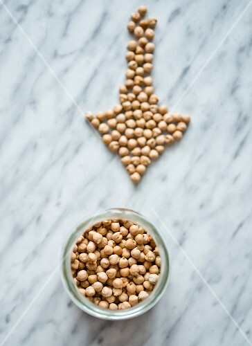 A jar of chickpeas and some arranged in an arrow shape