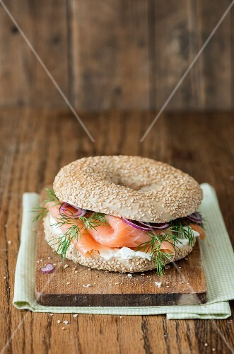 A bagel with cream cheese, salmon, dill and red onions