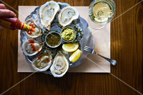 Oysters with hot sauce, lemon wedges, horseradish sauce and red wine mignonette