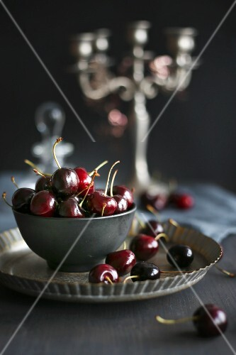 Cherries in a bowl on a metal plate