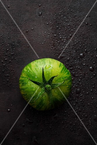 A green striped tomato on a black surface