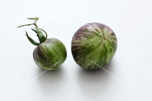 Two green striped tomatoes on a white surface
