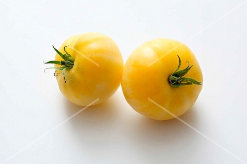 Two yellow tomatoes on a white surface