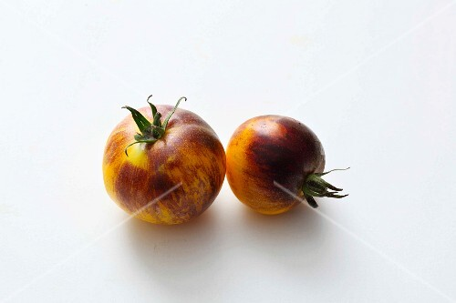 Two yellow-and-black tomatoes on a white surface
