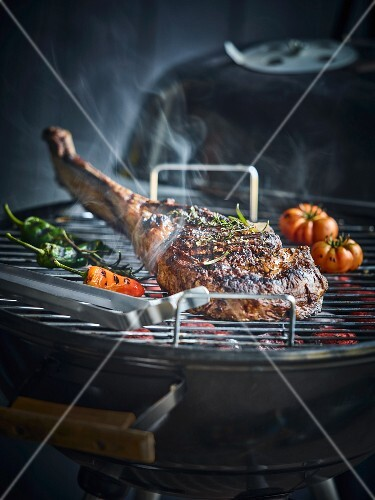 Tomahawk steak on a kettle barbecue