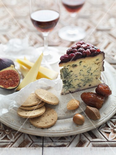A cheeseboard with crackers, figs, nuts and dates