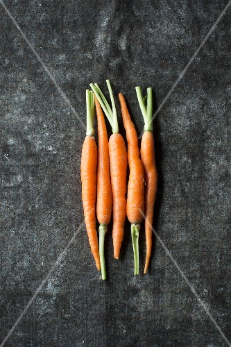 Five baby carrots next to each other on a grey surface
