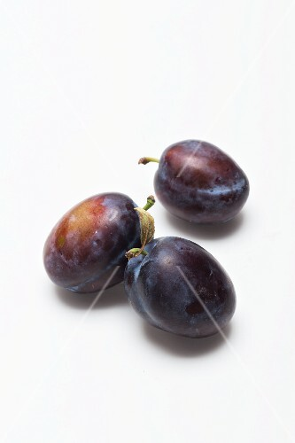 Three damsons on a white surface