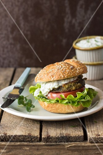 A burger with fried aubergine, tzatziki, tomato and lettuce