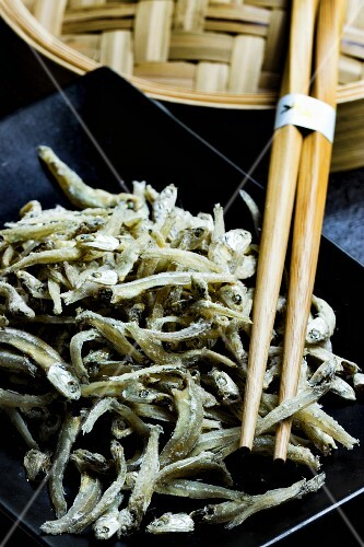 Chirimen (dried Japanese anchovies) with chopsticks and a bamboo steamer on a black plate