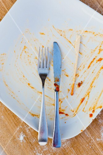 An empty plate with cutlery, a wooden skewer and the remains of sauce