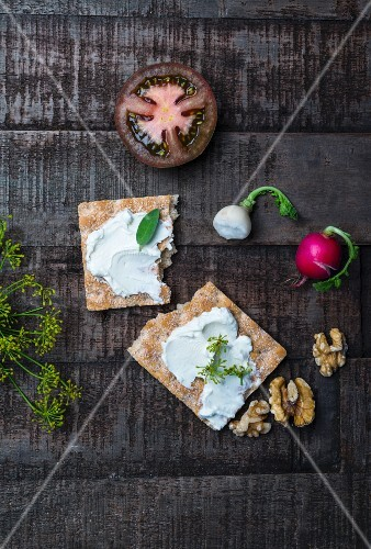 Crispbread with cream cheese, sage and dill, red and white radishes, sliced tomatoes and walnuts