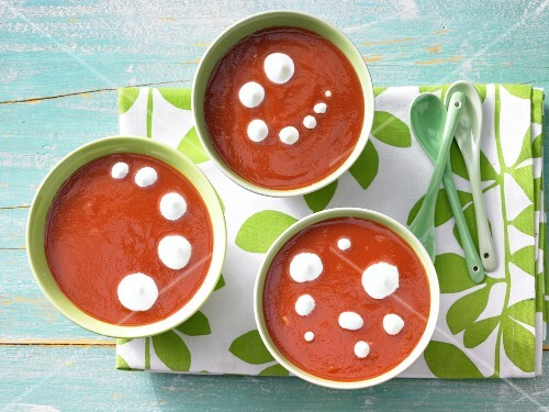 Orange and tomato soup with cream rosettes