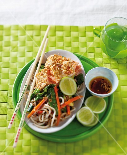 Salmon with a sesame seed coating served with noodles and vegetables