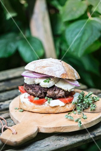 A lamb burger with goats' cheese, red onions, thyme and tomato