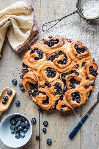 A crown of sweet yeast buns with blueberries and icing sugar (seen from above)
