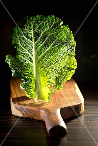 A leaf of savoy cabage on a chopping board