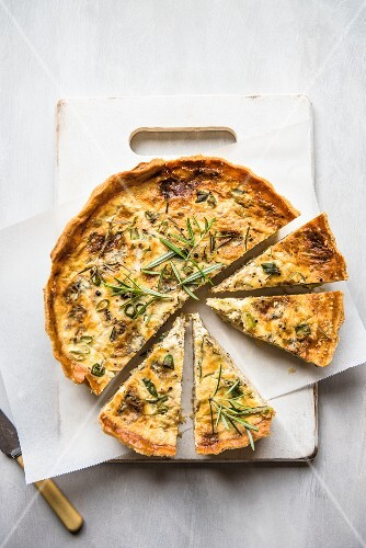 A sliced cheese & onion quiche with rosemary