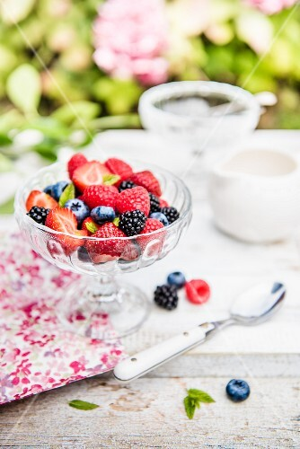 A summer berry salad with mint in a glass bowl on a garden table