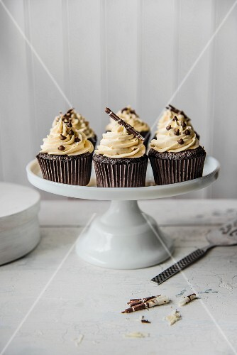Chocolate cupcakes with white chocolate icing on a cake stand