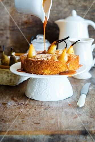 Vanilla cake with poached pears, flaked almonds and caramel sauce