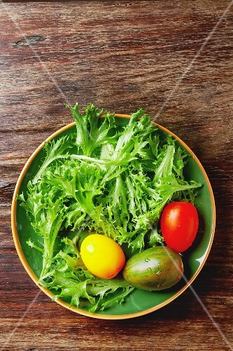 Fresh green salad leaves with colourful tomatoes (seen from above)