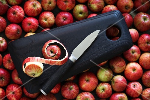 A wooden chopping board with a knife on red apples
