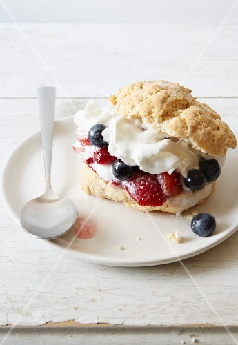 A scone with berries and cream