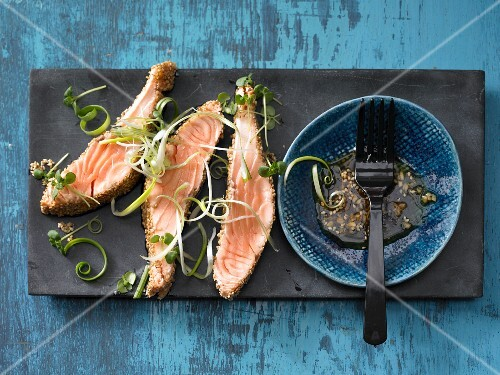 Salmon with a sesame seed coating served with spring onions and Shiso cress