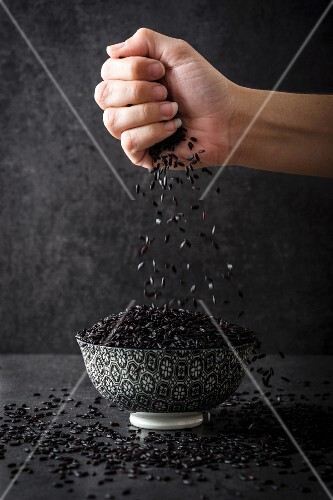 A hand drizzling black rice into a bowl