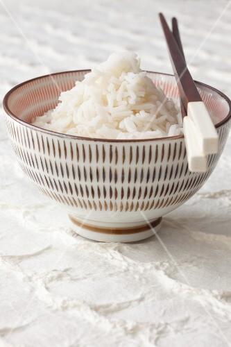 Boiled rice in a bowl with chopsticks