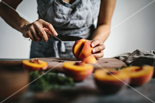 A woman s hands are photographed as she is slicing peaches