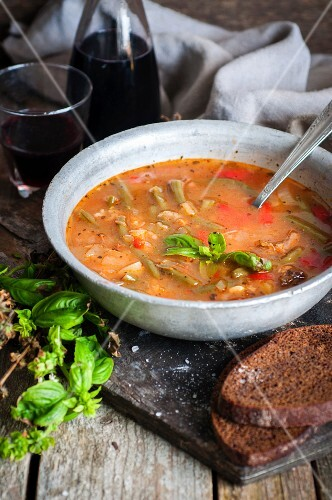 Rustic minestrone soup with tomatoes, green beans and basil